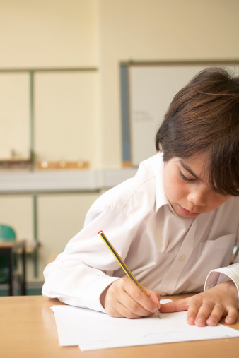Boy writing in classroom - gettyimageskorea