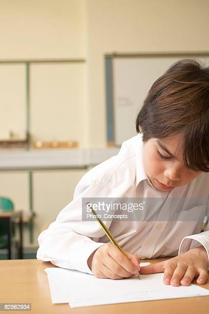 Boy writing in classroom