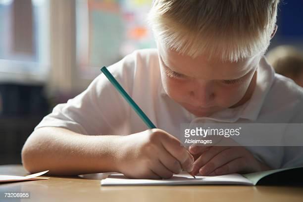 boy (5-7) writing in exercise book in classroom - schulheft stock-fotos und bilder