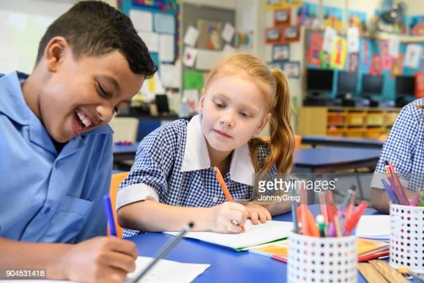 彼の学校の本を書いて、笑みを浮かべて少女を監視し、コピーの少年