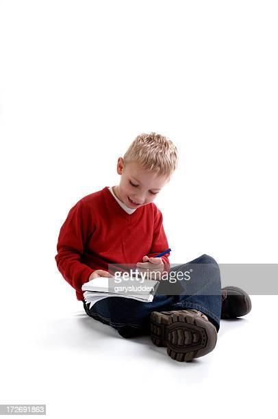 boy escribiendo en el cuaderno de notas