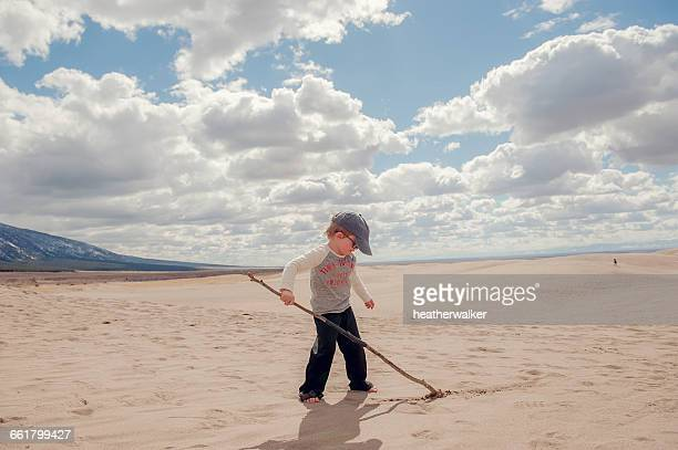 boy writing in sand with stick, grand sand dunes national park, colorado, america, usa - great sand dunes national park stock pictures, royalty-free photos & images