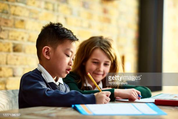 boy writing in workbook with sister watching at dining table - talking stock pictures, royalty-free photos & images