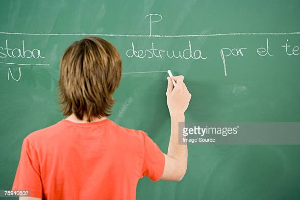 boy writing on blackboard - iberian ethnicity stock pictures, royalty-free photos & images
