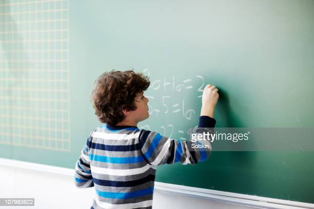 boy writing on board in school class - mathematics stock pictures, royalty-free photos & images