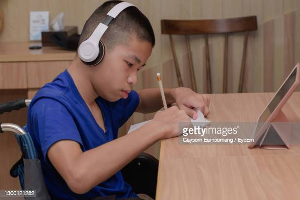 boy writing on paper at table - leaning disability stock pictures, royalty-free photos & images