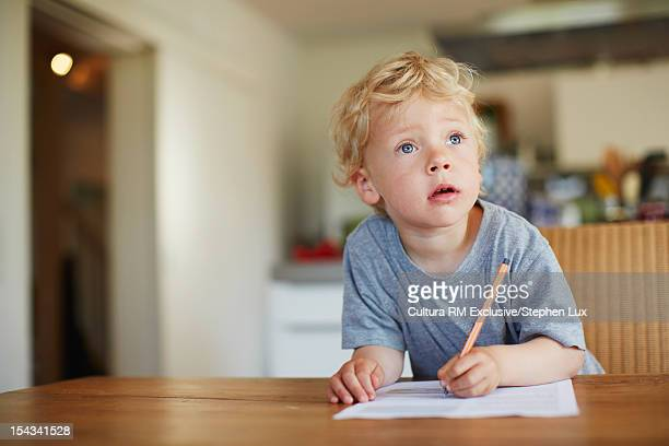Boy writing on paper at table