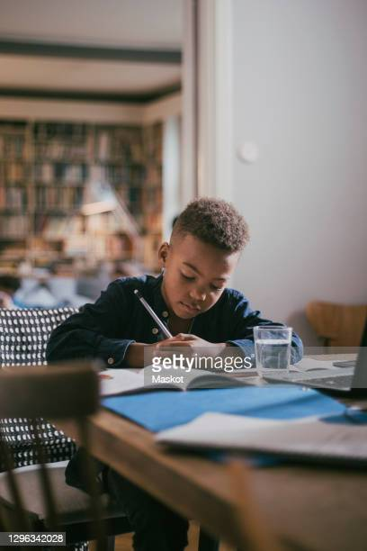 boy writing while studying over table at home - education stock pictures, royalty-free photos & images
