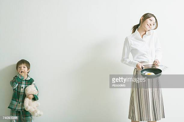 a boy yawning, a woman cooking an egg - yawning mother child stock photos and pictures