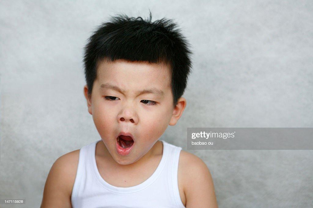 Boy yawning on grey background : Bildbanksbilder