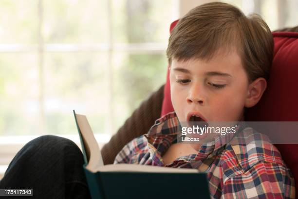 Boy Yawning while Reading a Book