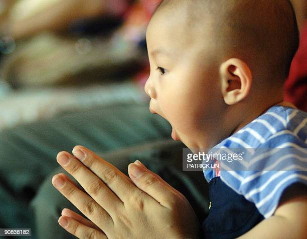 A boy yawns as his mother prays during a ceremony to confort victims of Typhoon Morakot in Kaohsiung southern Taiwan on September 1 2009 The Dalai...