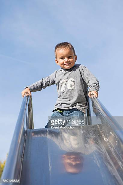 boy young playground slide kneeling sliding - dreiviertelansicht stock pictures, royalty-free photos & images