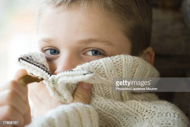 Boy zipping collar of wool sweater over face, close-up