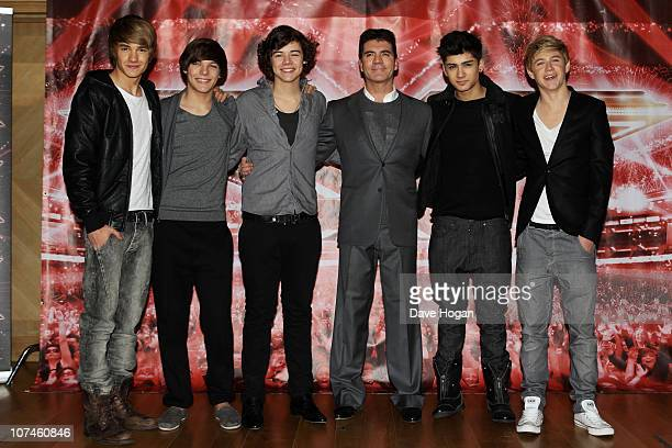 Boyband One Direction pose with Simon Cowell for a photocall to promote the XFactor final held at The Connaught Hotel on December 9 2010 in London...