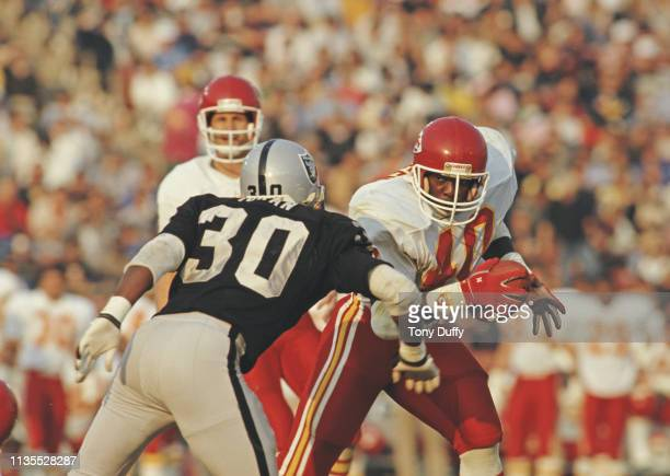 Boyce Green, Running Back for the Kansas City Chiefs attempts to pass Stacey Toran, Strong Safety for the Los Angeles Raiders during their American...