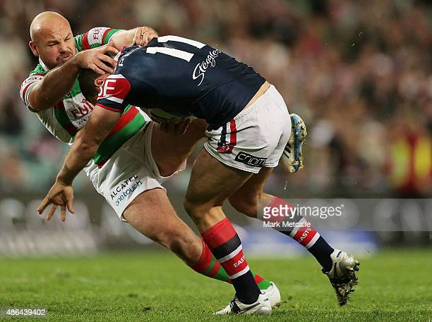 Boyd Cordner of the Roosters is tackled by Glenn Stewart of the Rabbitohs during the round 26 NRL match between the Sydney Roosters and the South...