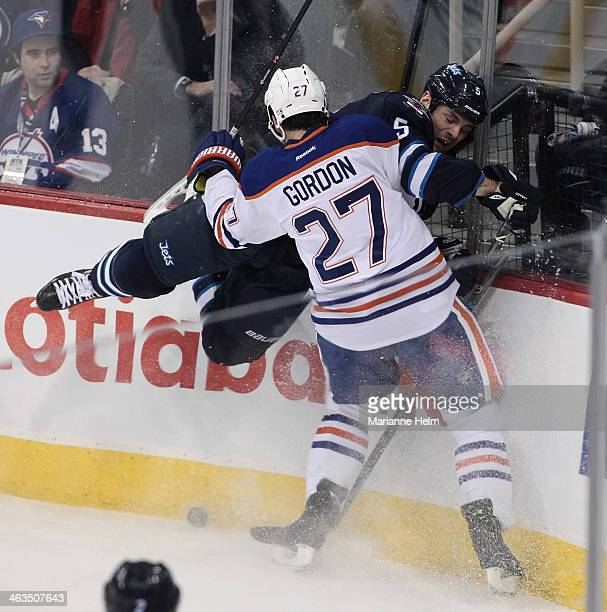 Boyd Gordon of the Edmonton Oilers and Mark Stuart of the Winnipeg Jets collide along the boards in first period action in an NHL game at the MTS...
