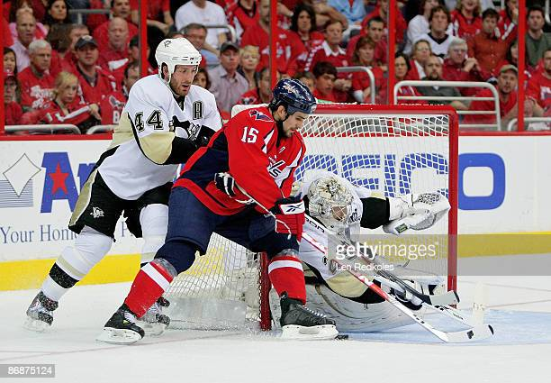 Boyd Gordon of the Washington Capitals tries to stuff a shot on goal between Brooks Orpik and MarcAndre Fleury of the Pittsburgh Penguins during Game...