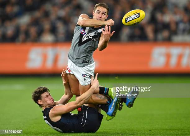 Boyd Woodcock of the Power handballs whilst being tackled by Sam Walsh of the Blues during the round five AFL match between the Carlton Blues and the...