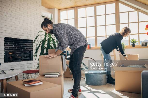 boyfriend and girlfriend unpacking boxes in new apartment - box container stock pictures, royalty-free photos & images
