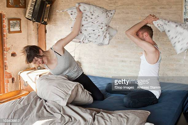 A boyfriend and his girlfriend having a pillow fight in bed