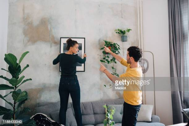 boyfriend guiding girlfriend in hanging picture frame on wall at new home - mid adult men stock pictures, royalty-free photos & images
