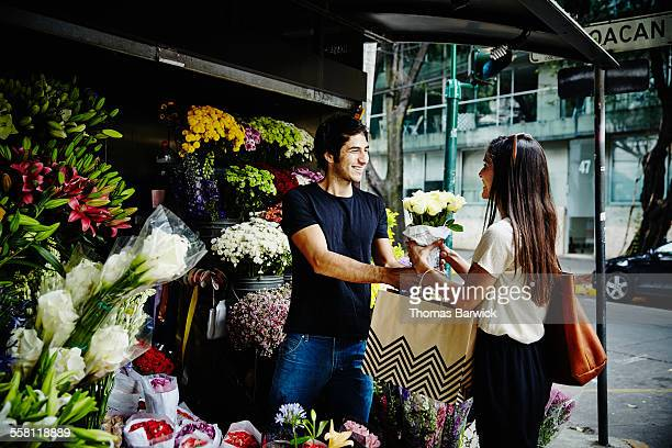 Boyfriend handing bouquet of roses to girlfriend