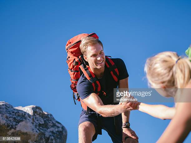 Boyfriend helping woman to climb mountain during backpack outdoo