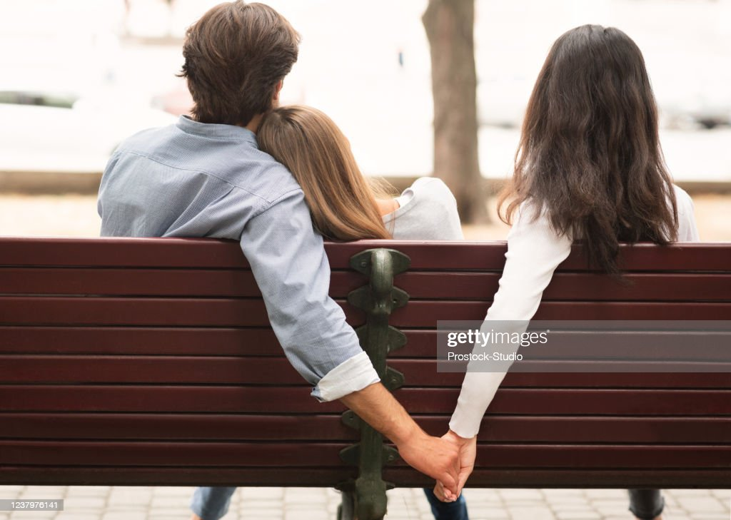 Boyfriend Holding Hands With Girlfriend's Friend Sitting On Bench Outdoor : Stock Photo