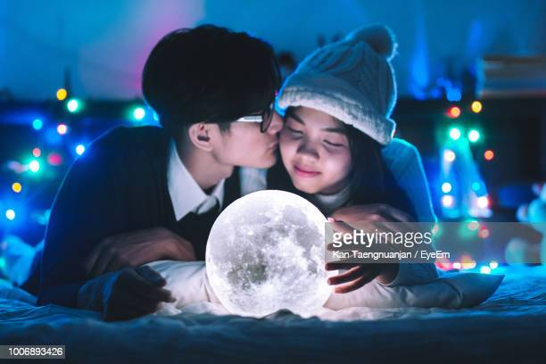 boyfriend kissing girlfriend by illuminated moon light decoration on bed - moonlight lovers stock-fotos und bilder