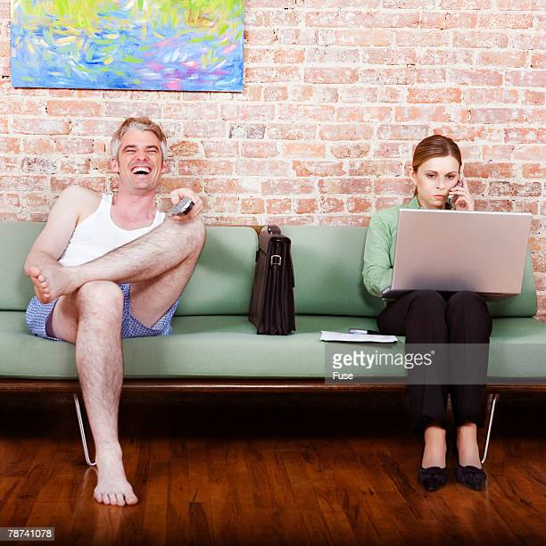 Boyfriend Laughing at TV While Professional Girlfriend Works