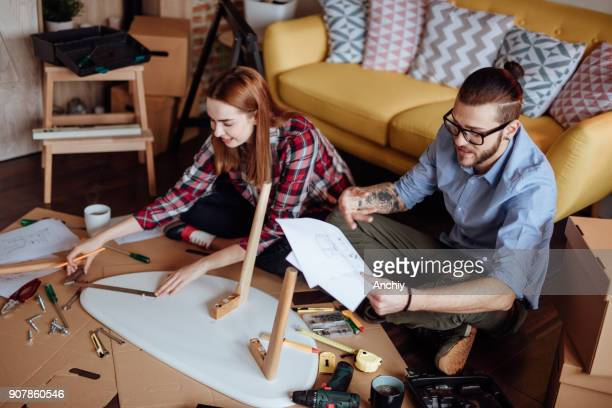 Boyfriend looking at manual while girlfriend measuring table