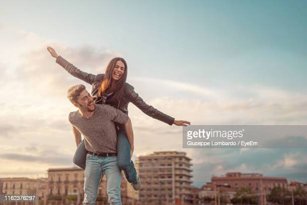 boyfriend piggybacking girlfriend in city against sky - heterosexual couple stock pictures, royalty-free photos & images