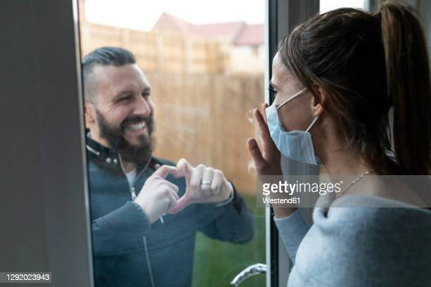 boyfriend show heart shape gesture to girlfriend through window glass while during covid-19 crisis - lockdown stock pictures, royalty-free photos & images