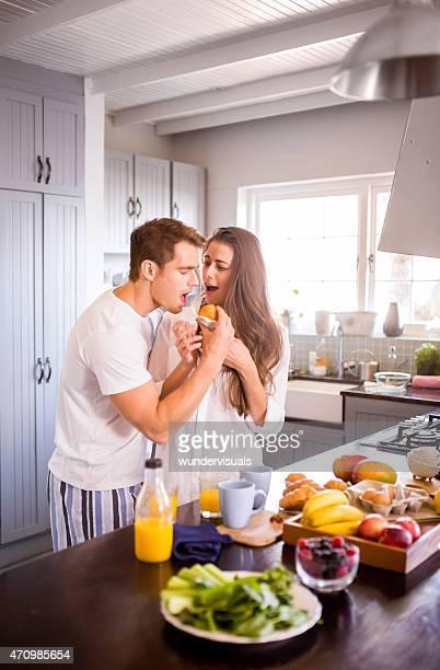 boyfriend stealing his girlfriend's muffin in the morning - steel stockfoto's en -beelden