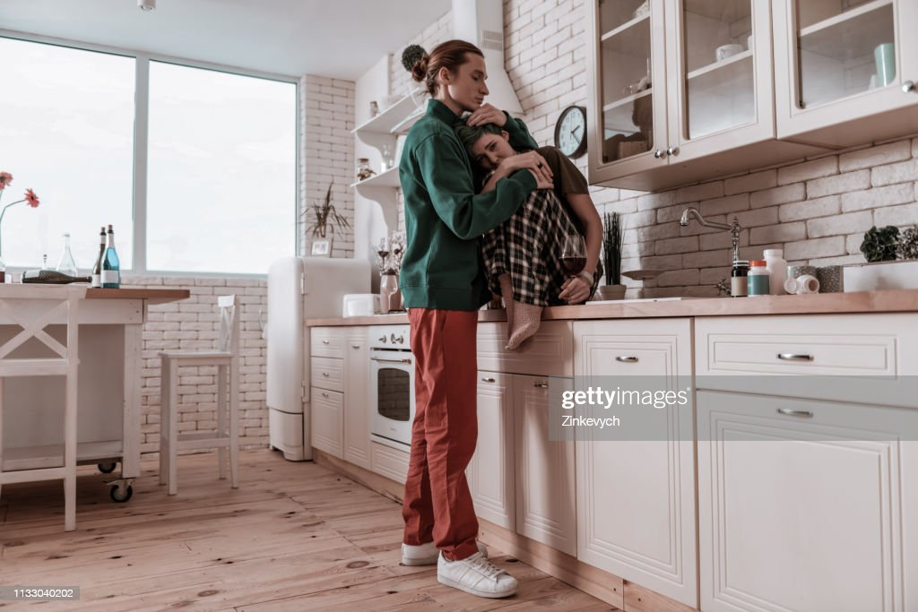 Boyfriend wearing red trousers hugging his tender little girl : Stock Photo