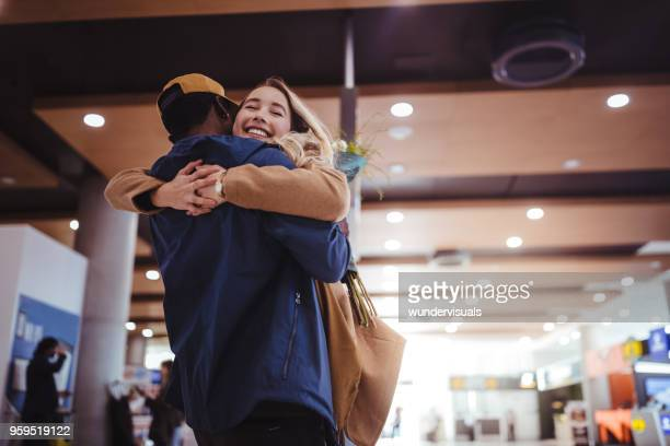 boyfriend welcoming and embracing excited girlfriend at airport - arrival stock pictures, royalty-free photos & images
