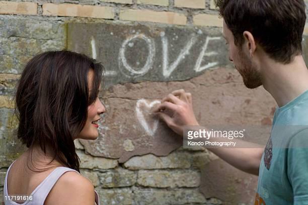 Boyfriend writing LOVE on a wall
