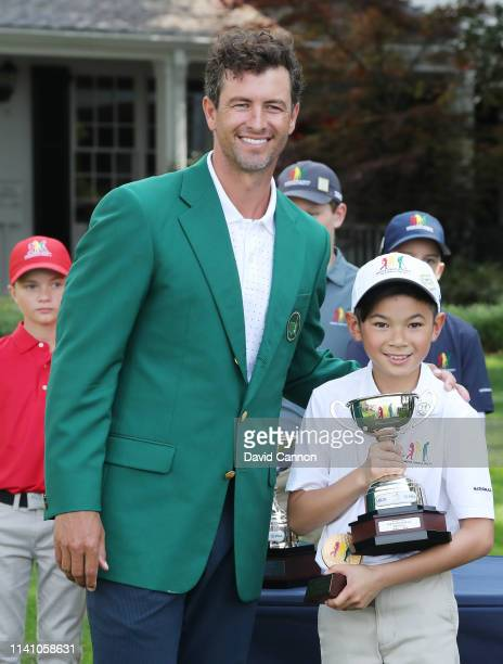 Boys 1011 group third place finisher Aiden Tiet poses with his trophy and Adam Scott of Australia during the Drive Chip and Putt Championship at...