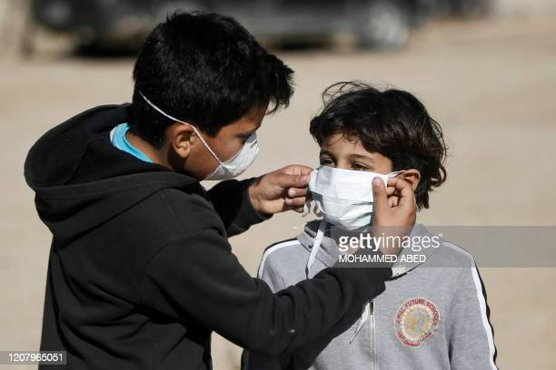 A boys adjusts the protective mask of another in a street outside their homes in Gaza City on March 22 2020