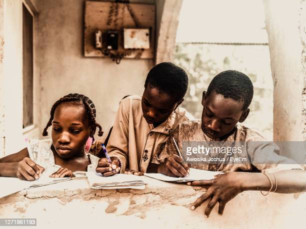 boys and girl at table - nigeria stock pictures, royalty-free photos & images