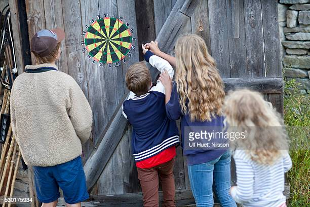 Boys and girl checking dartboard