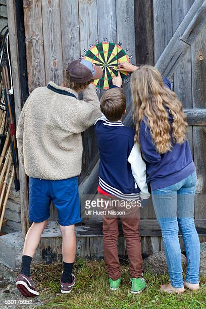 boys and girl checking dartboard - darts girls stock photos and pictures