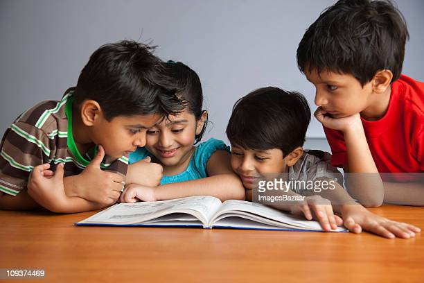 Boys (6-7) and girl (4-5) enjoying reading children's book