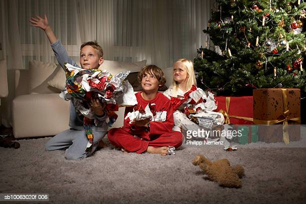 Boys and girl (6-9) holding wrapping paper