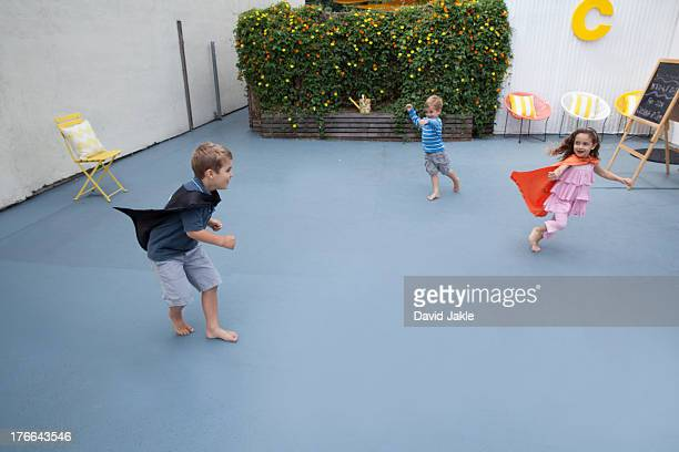 Boys and girl wearing superhero capes playing in back yard