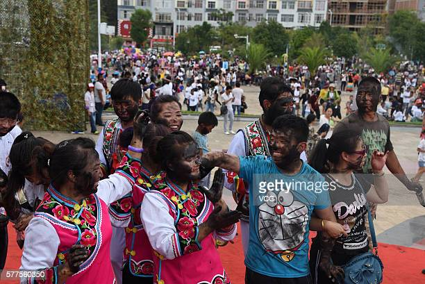 Boys and girls are daubed rice ash on faces during the Face Painting Festival in Puzhehei Resort of Qiubei County on July 18, 2016 in Wenshan...