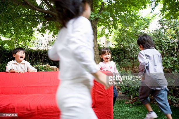 Boys and girls are playing by red sofa in garden
