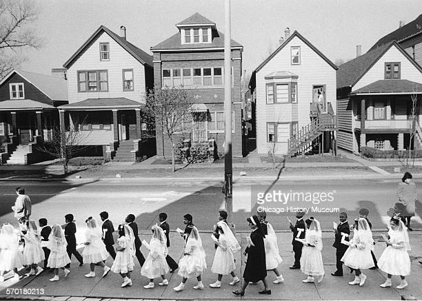 Boys and girls dressed for their First Holy Communion walking on the sidewalk near St Michael's Catholic Church 82nd and South Shore Drive Chicago...